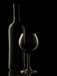 Red wine bottle and glass on black background