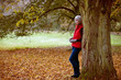 A woman standing next to a tree in autumn time