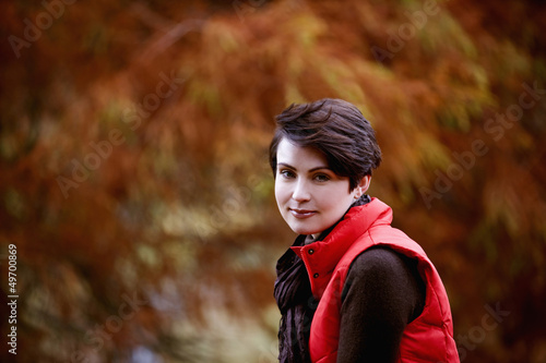 A woman sitting on a fence in autumn time, close up