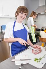 Junge hilft der Mutter beim Kochen in der Küche