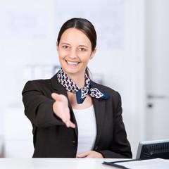 freundliche mitarbeiterin reicht die hand