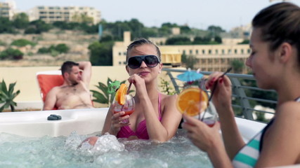 Female friends relaxing in jacuzzi with exotic coctails, slow mo