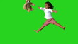 Little girl jumping on green screen and catching teddy