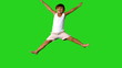 Happy little boy jumping on green screen