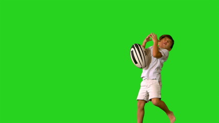 Happy little boy jumping and dropping rugby ball