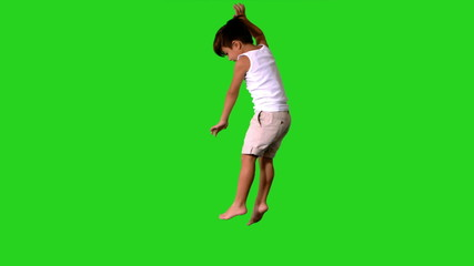 Happy little boy jumping and spinning on green screen