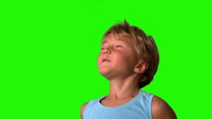 Little boy heading football on green screen