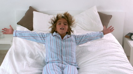 Little boy jumping back onto bed