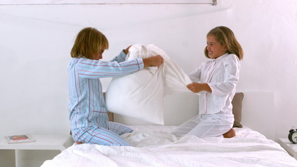 Siblings having a pillow fight on the bed