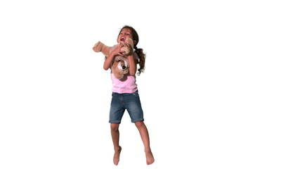 Cute little girl jumping and catching teddy on white background