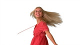 Attractive blonde twirling on white background