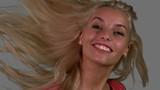 Attractive blonde shaking her hair on grey background