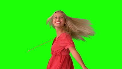 Attractive blonde twirling on green screen