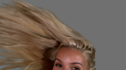 Attractive blonde tossing her hair up on grey background