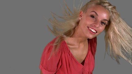 Attractive blonde tossing her hair on grey background