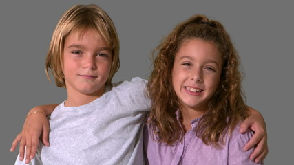 Siblings smiling on grey background