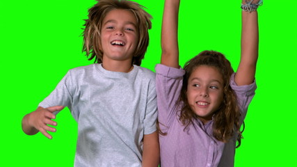 Brother and sister jumping up on green screen