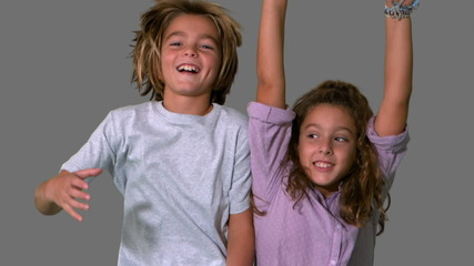 Brother and sister jumping up on grey background