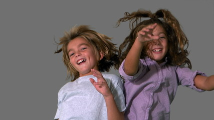 Brother and sister jumping up and crashing on grey background