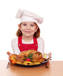 beautiful little girl cook with roasted chicken on table