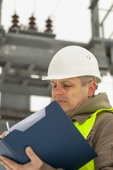 Engineer with folder on a transformer background