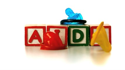 Colourful condoms falling on blocks spelling AIDS