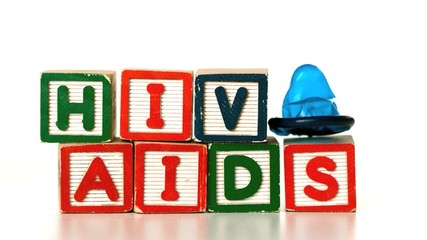 Blue condom falling on blocks spelling AIDS and HIV
