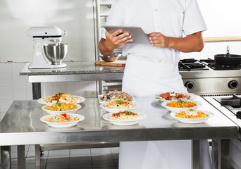 Chef Using Digital Computer In Kitchen