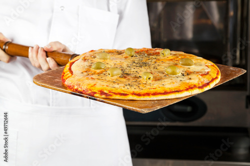 Chef Holding Pizza On Shovel