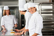 Female Chef With Colleagues In Commercial Kitchen