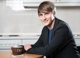 Junger Mann frühstückt in der Küche mit einem Kaffee