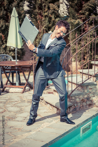 Angry Businessman with Computer next to Swimming Pool
