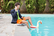 Funny Young Businessman with SwimmingTrunks next to the Pool