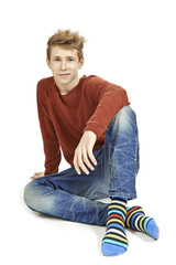 Trendy young man sitting down smiling