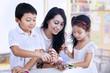 Happy teacher and preschooler paint easter eggs