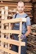 Warehouse worker moving wood pallets