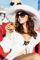 The beautiful glamour girl in a white hat on the beach