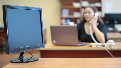 Monitor screen in focus and call center operator on backgroung