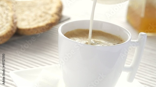 slow motion adding milk  in coffee