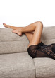 Long Woman legs in stockings on sofa. sexy women legs on sofa .