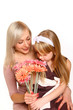 Happy mother and daughter sniffing flowers isolated