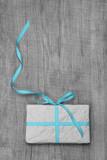 Geschenk mit türkisfarbener Schleife auf Holz Hintergrund