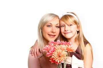 Smiling mother and daughter with flowers hugging  isolated on wh