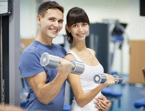 Cheerful young couple in a gym