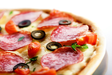 Pizza with salami and black olives. macro