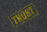Trust word stamped on asphalt background