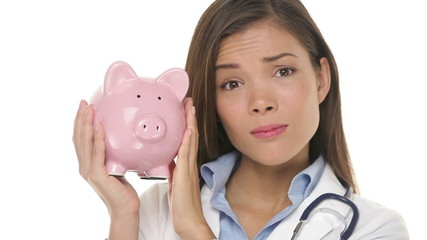 Sad doctor holding piggy bank, health care concept