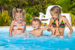 two little girls and little boy playing in the pool