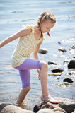 Girl goes to shore of water in sunny day