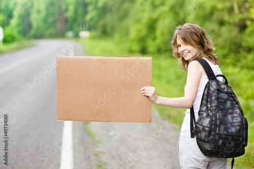 young tourist hitchhiking along a road with message board